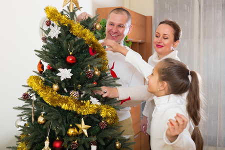 Parents and child preparing for Christmas at living room photo
