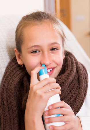 catarrh: Sick schoolgirl sitting on couch with nasal sprayer for rhinitis