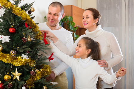 decorating christmas tree: Happy parents and girl decorating Christmas tree in the living room at home Stock Photo