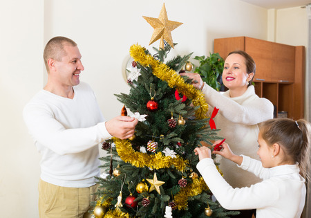 Happy smiling parents and girl decorating Christmas tree in the living room at home. Focus on man photo