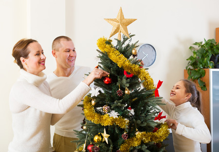 Happy parents and their child preparing for Christmas at living room photo