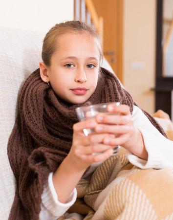 enfant malade: Sick petite fille habill�e en �charpe chaude potable � partir de verre sur le canap� � la maison