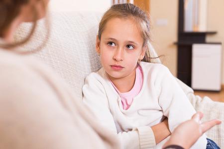 dialogo: Madre rega�ar peque�a hija colegiala en el sof� en casa Foto de archivo