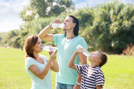 man drinking water: parents with teenager son drinking water from plastic bottles in summer park