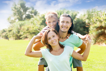 Happy parents with teenager son in summer park photo