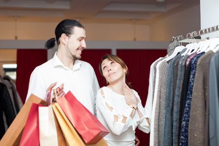 Two happy buyers with shopping bags  at clothing shop photo