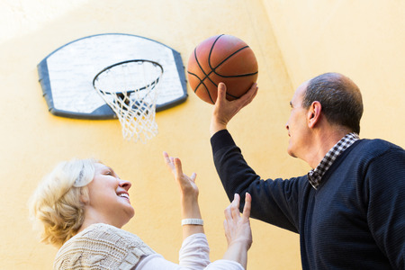 Happy active senior mature couple playing basketball in patio photo