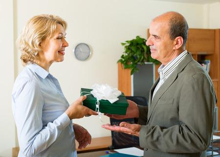 SECRETARIA: Secretaria sonriente mujer felicita jefe en d�a de los hombres en la oficina