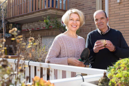 sundry: Happy smiling aged woman with horticultural sundry and aged man drinking tea in patio. Focus on woman