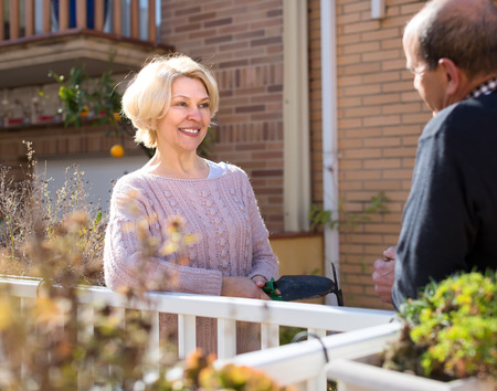 Mature couple having a conversation on a terrace: retired woman is holding her gardening tools and man holds a cup of water