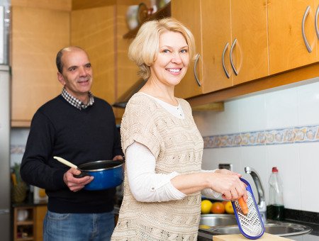 spouses: Happy smiling senior mature spouses preparing meal together in kitchen at home
