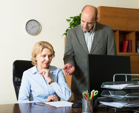 unprofessional: Angry boss screaming at careless elderly female secretary in office