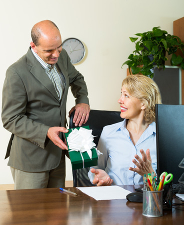 congratulating: Manager congratulating smiling female secretary on Womens Day Stock Photo