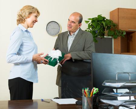 Female secretary congratulates boss on Mens Day in office