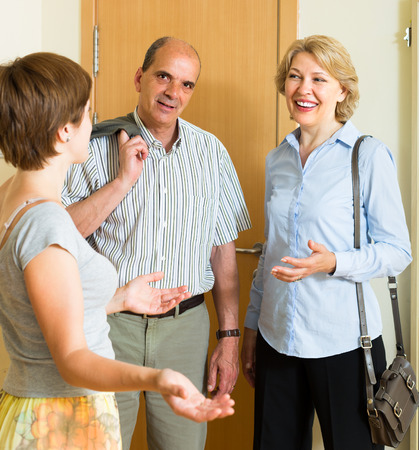 Young woman meeting smiling mature friends at the door