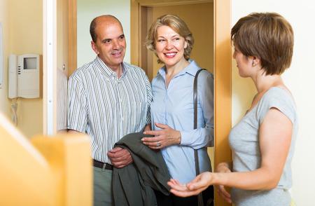 threshold: Adult daughter greeting smiling elderly parents at threshold Stock Photo
