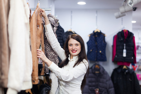 clothing store: Young woman choosing jacket at clothing store Stock Photo