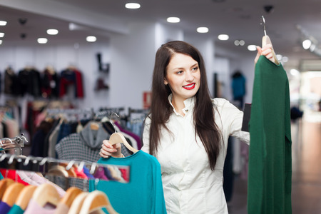 'pull over': Happy female buyer with two sweaters at clothing store Stock Photo