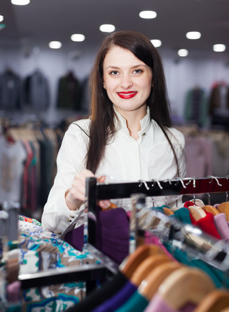 gladful: Smiling female buyer choosing clothes at fashionable shop