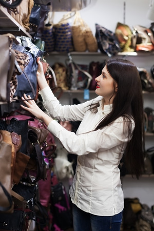 leather bag: Ordinary girl choosing leather bag at store Stock Photo