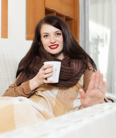 Long-haired girl with cup near electric calorifer  in home