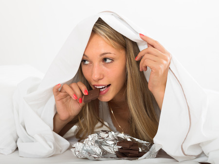 furtively: Long-haired beautiful  woman eating  chocolate  in bed at home
