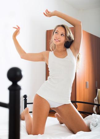 awaking: Sexy woman awaking on white sheet in bedroom