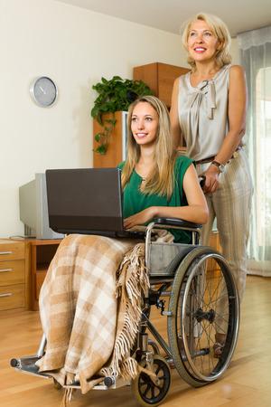 paraplegico: Mujer madura y una ni�a con discapacidad usando la computadora port�til en interiores. Centrarse en los j�venes