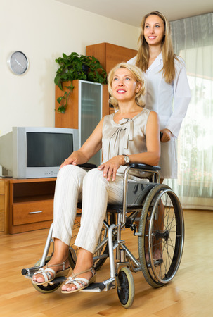 incapacitated: Friendly physician and smiling disabled woman on chair communicating indoor
