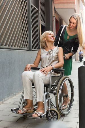 incapacitated: Friendly smiling social worker and disabled mature woman on chair at stroll