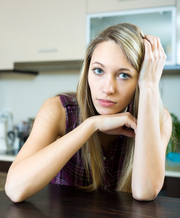 aloneness: Troubled woman is sitting at the kitchen table indoors