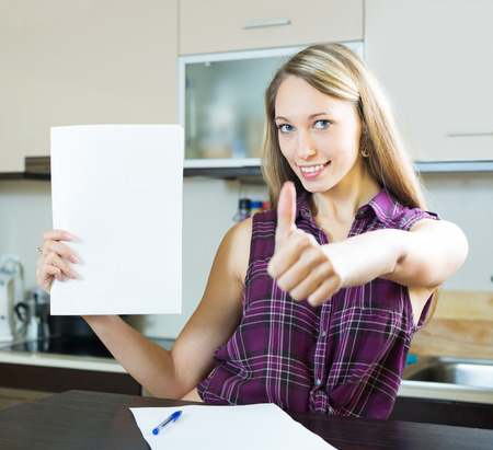cheeful: Cheerful long-haired woman reading documents in kitchen Stock Photo