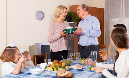 relatives: Happy family member receiving present from relatives at table Stock Photo