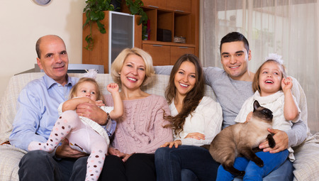 big and small: Long family with grand children posing indoors Stock Photo