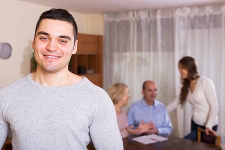 familia unida: Adulto hombre sonriente permanecer cerca de sus familiares unidos
