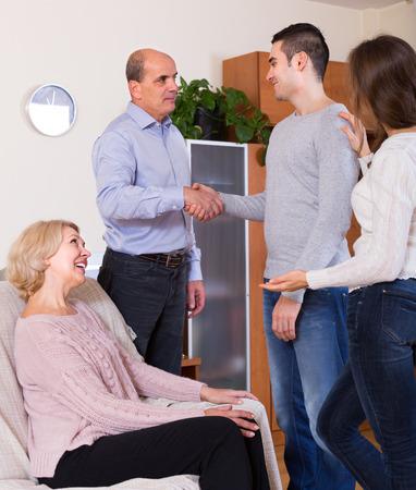 introducing: Adult daughter introducing her boyfriend to happy parents indoor