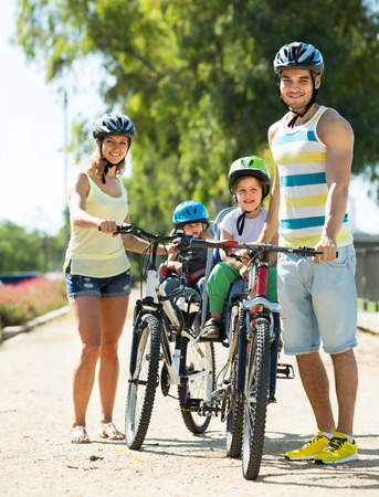 Happy young family of four cycling on street road in summer day