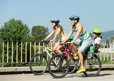 andando en bicicleta: Joven familia de cuatro personas con bicicletas en cascos de deportes al aire libre
