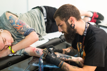 17th: BARCELONA, SPAIN - OCTOBER 3, 2014: Professional artist  doing   tattoo on client arm. The 17th edition of The Barcelona Tattoo Expo in Fira de Barcelona