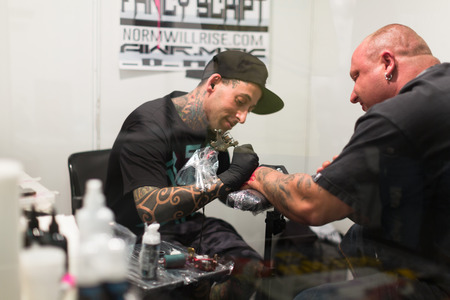17th: BARCELONA, SPAIN - OCTOBER 3, 2014: Professional artist  doing colorful tattoo on client arm. The 17th edition of The Barcelona Tattoo Expo in Fira de Barcelona