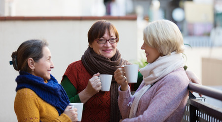 chat group: Mature women in warm clothes having cup of hot tea on terrace Stock Photo