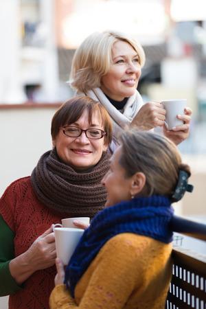 2 50: Group of positive senior women drinking tea at balcony. Focus on brunette