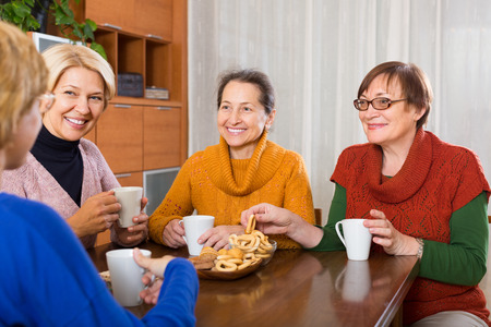 Smiling senior female friends drinking coffee and talking