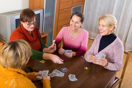 Several happy female pensioners playing cards at home photo