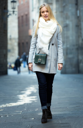 warmly: Beautiful young woman walking on a street outdoors warmly dressed on a cold autumn day