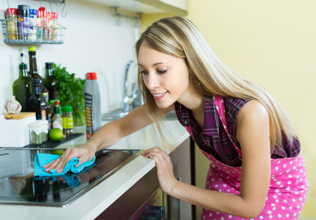 tidying up: Young housewife tidying up kitchen-range after cooking and smiling