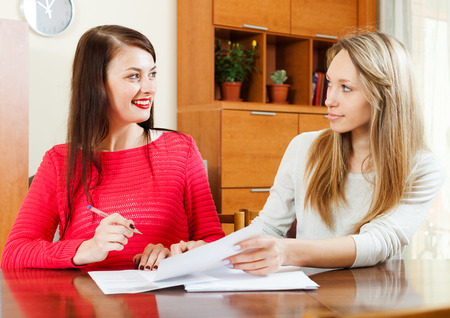 home office interior: women with  documents  at table in home or office interior