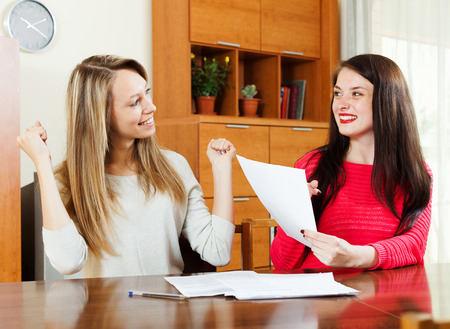 parsimony: Happy women with financial documents  at table in home or office interior