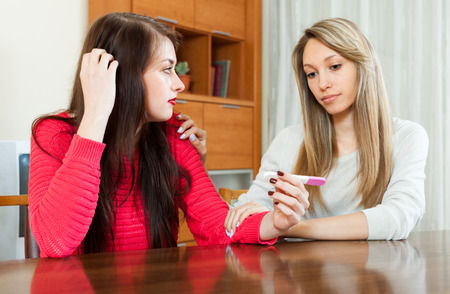 home pregnancy test: Sad girl with pregnancy test, girlfriend consoling her in home Stock Photo