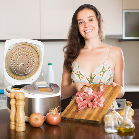 Smiling housewife cooking meat with multicooker in home interior photo